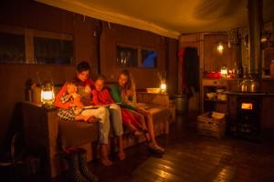 Coin salon éclairé aux bougies au glamping Un lit au Pré à La Ferme de Penquelen Huella à Scaër en Bretagne