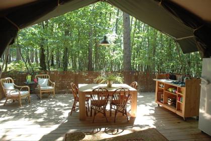 Coin repas et terrasse tente safari au glamping Le Grand Bois à Le Poët Célard en Rhône-Alpes