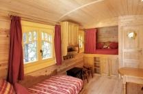 Intérieur de la roulotte : coin salon et lit alcove au glamping DéfiPlanet' à Dienné en Poitou-Charentes