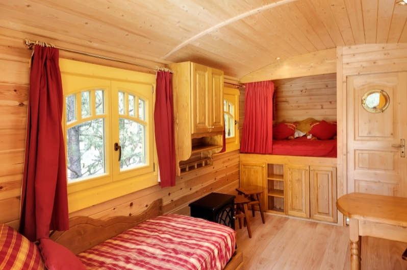 int rieur de la roulotte coin salon et lit alcove glamping en france. Black Bedroom Furniture Sets. Home Design Ideas