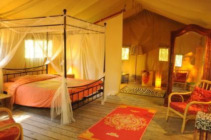Intérieur tente safari et lit à baldaquin au glamping Le Grand Bois à Le Poët Célard en Rhône-Alpes