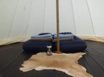Intérieur du tipi avec plancher bois et peau de vache au glamping Camping des Cerisiers à Guillac en Bretagne