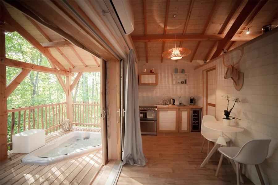 Coin cuisine, terrasse et jacuzzi du Natura Lodge au glamping d'Emilion de Sens à Gardegan et Tourtirac en Aquitaine